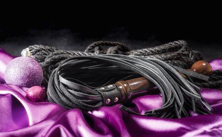 bdsm still life leather black lash shibari rope and lilac christmas ball on pink cloth close up Stock Photo