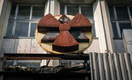 old rusty radioactive symbol on the facade of a building in Chernobyl close up