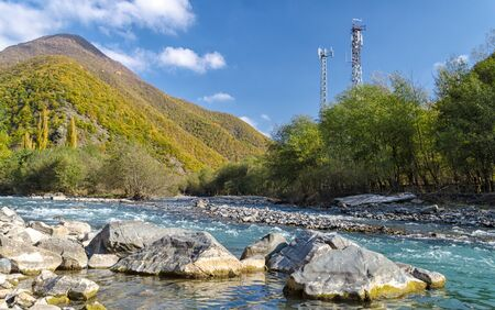 landscape with two cell towers near a mountain river