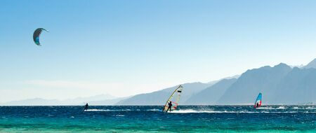 windsurfers and kitesurfers ride in the Red Sea on the background of the rocky coast in Egypt Dahab