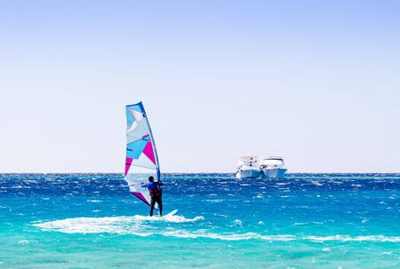 surfer rides in the Red Sea against the backdrop of two ships in Egypt Dahab