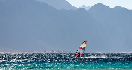 windsurfer rides in the Red Sea against the backdrop of high rocky mountains in Egypt Dahab Stok Fotoğraf