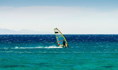 windsurfer on the background of mountains rides on the waves of the Red Sea in Egypt Dahab