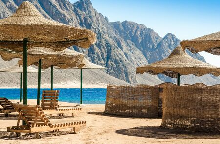 beach umbrellas and wooden lounge chairs on the sand of the beach against the backdrop of the sea and high rocky mountains