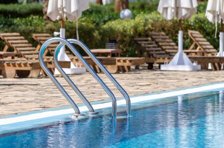 handrails by the pool with blue water on the background of sun loungers and folded white umbrellas Stok Fotoğraf