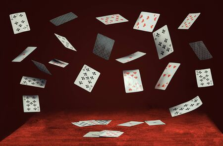 playing cards fly and fall on a table with red cloth