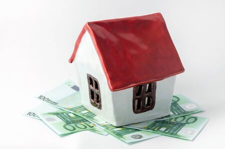 small white porcelain house with a red roof and money euro banknotes rent purchase realtor on a white background isolated