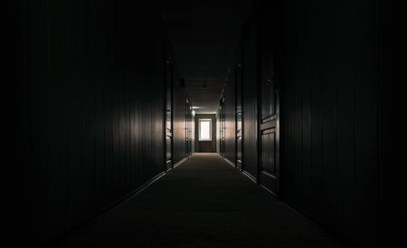 gloomy dark corridor with closed doors of an empty hotel without people during quarantine