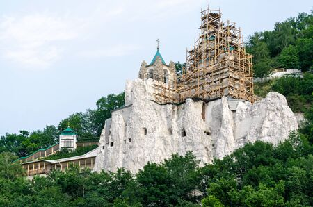 restoration of a christian church on a stone rock mountain in a forest without people