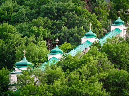 domes of a christian church in a green forest without people