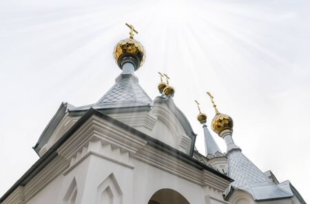 golden domes with crosses of the Christian church and heavenly rays of light from the sky