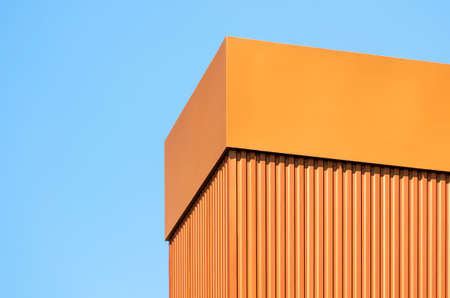 orange wall of a modern building on a background of blue sky simple architectural abstract background pattern