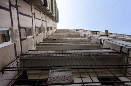 old gray tall building without people in Ukraine Donbass bottom view Stock Photo