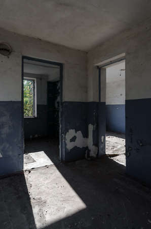 room with windows and a door of an old abandoned house in Ukraine after the war