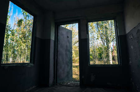 view of the forest from a room with windows and a door of an old abandoned house in Ukraine after the war