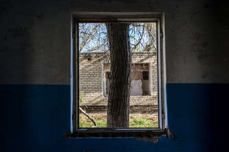 view from the window of an abandoned abandoned house in the village of Ukraine during the war Stok Fotoğraf