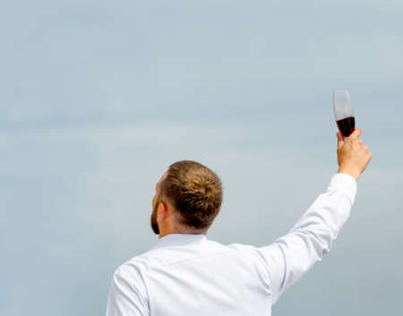 office employee man in a white shirt with a glass of wine in a raised hand