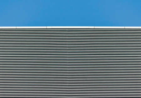 striped wall of a gray tall building against a blue sky