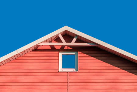 roof of pink farmhouse wooden house against blue sky background rustic architecture