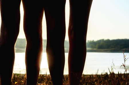 silhouette of male and female legs without clothes on the river bank