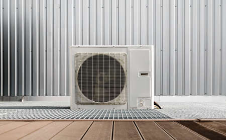 one modern air conditioner on a gray wall background