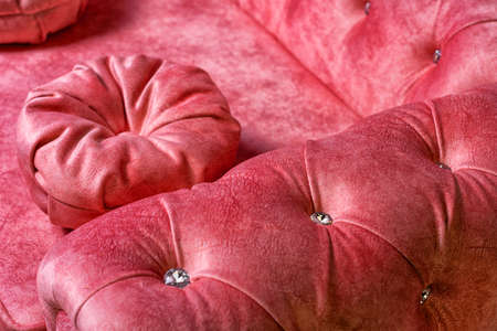 red soft sofa with large rhinestones close-up