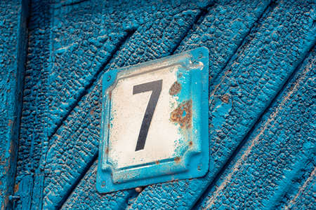 outdoor old blue painted door with number seven