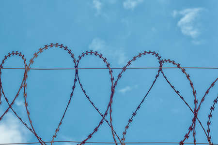 rusty barbed wire on blue sky background