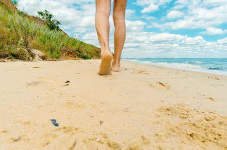 man's naked legs walks barefoot along the beach towards the city Stok Fotoğraf