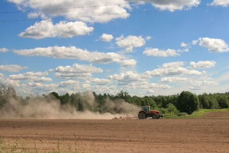 brigth: a tractor on a tillage in the daytime Stock Photo