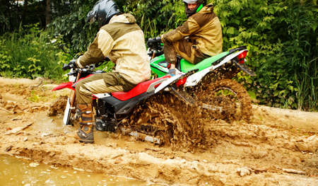 Motocross racers racing on the off-road circuit mud flying through air. Motorbike rides through the mud with big splash,driver splashing mud on wet and muddy terrain, Motocross racer in a wet and muddy. Stock Photo