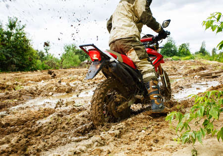 The man on a motorcycle rides through the mud Imagens