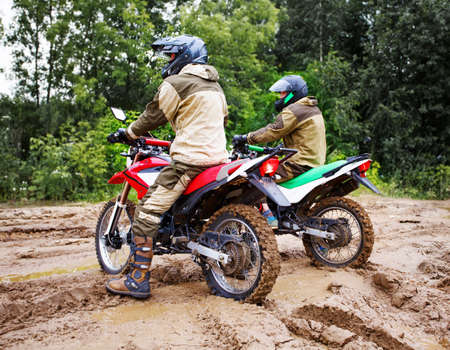 Two mens on a motorcycle rides through the mud Stock Photo