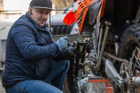 mechanic fixing motocycle wheel