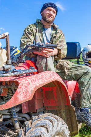 Relaxed man sits on an ATV