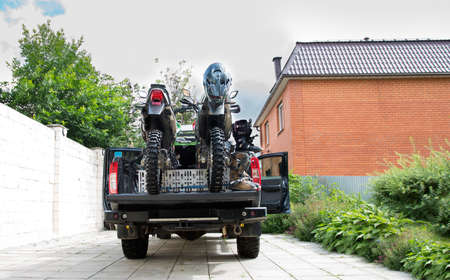 Two dirt bike motorcycles on the back of the camo truck with saf