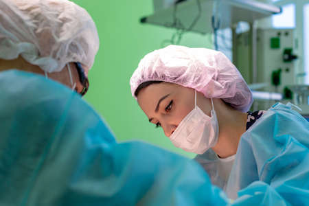 female surgeon doctor or intern wearing protective mask and hat.
