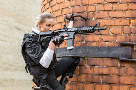Powerful Woman Holding Gun. War Action Movie Style Stock Photo