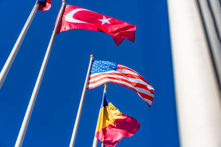 Flags of different countries flutters in the wind against