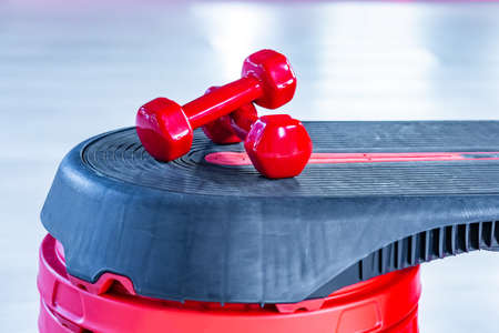 Red modern dumbbells in the foreground on a step platform 스톡 콘텐츠