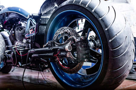 Cropped close up shot of beautiful and custom made motorcycle in the workshop Standard-Bild