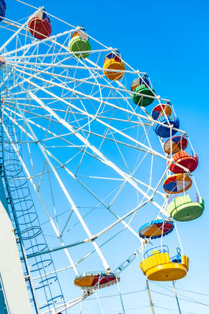 Colorful ferris wheel of the amusement park in the blue sky background Stockfoto