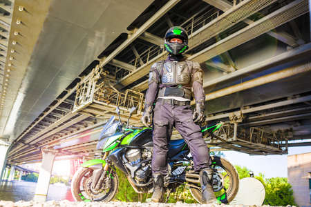 motorcyclist in a helmet and in a protective suit stands under t
