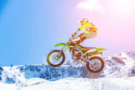 racer on a motorcycle in flight, jumps and takes off on a springboard against the snowy mountains Stock Photo