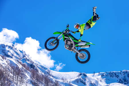 racer on a motorcycle in flight, jumps and takes off on a springboard against the snowy mountains 版權商用圖片