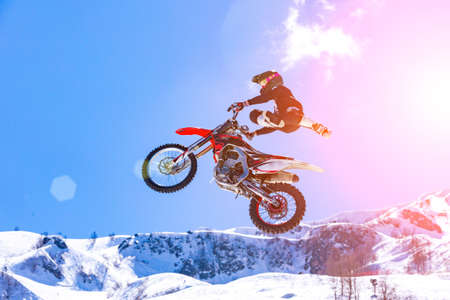 racer on a motorcycle in flight, jumps and takes off on a springboard against the snowy mountains Stockfoto