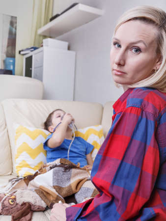 Sick child and mother . Sick chid with pediatric nebulizer. Little kid with asthma or bronchitis has trouble breathing.
