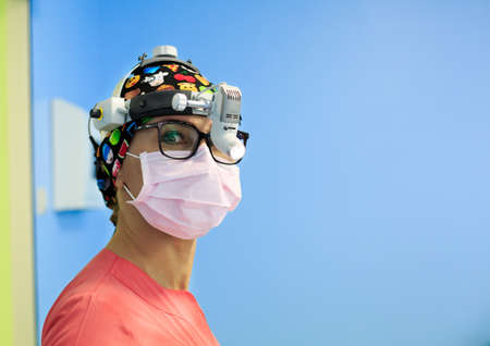 Female surgeon with a magnifying glass in operation room