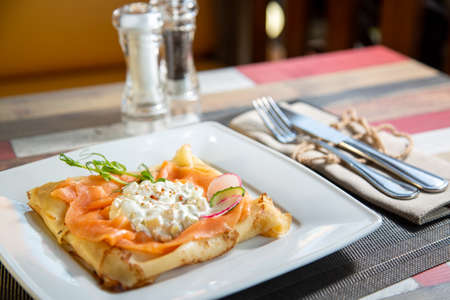 Pancake with salmon and sourcream and dille on a white plate.