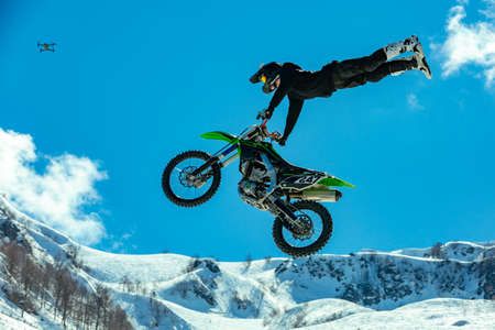 racer on a motorcycle in flight, jumps and takes off on a springboard against the snowy mountains Imagens